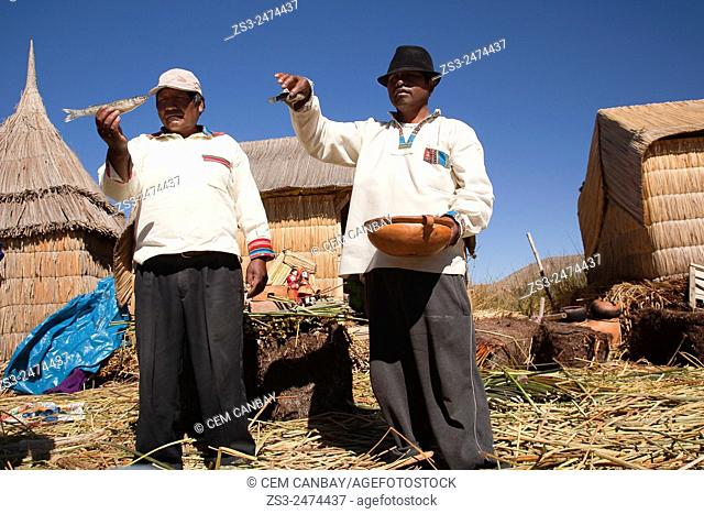 Aymara men showing some fish from their catch, Uros Islands, Lake Titicaca, Puno Region, Peru, South America