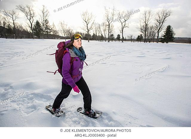 Woman with ski goggles and jacket snowshoeing outdoors in winter