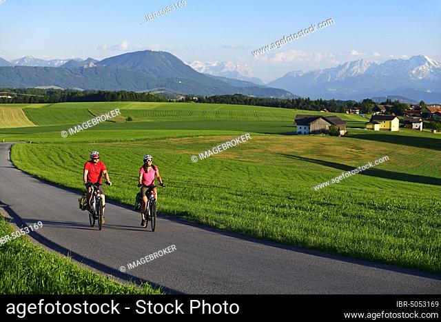 Couple with electric bikes at Sulzberg, Obertrum, in the background the Berchtesgaden Alps and the Dachstein Mountains, Salzburg Lakeland, Salzburger Land