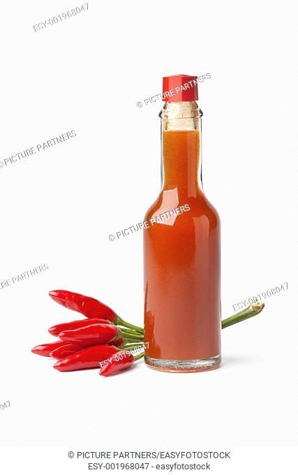 Bottle with hot chili pepper sauce and fresh tabasco peppers on white background