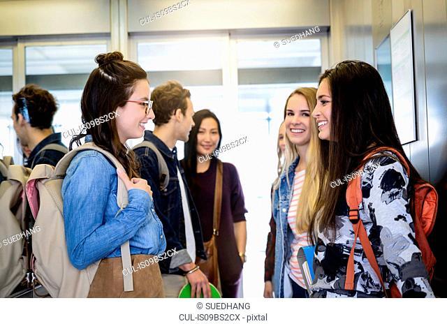 University students talking inside elevator