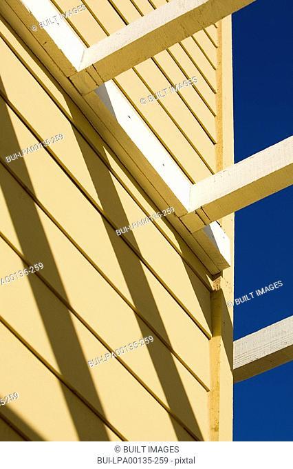 Detail yellow home with white trellis
