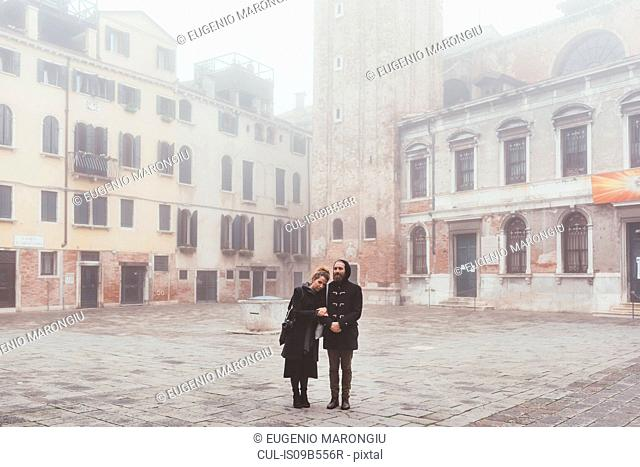 Portrait of couple in misty square, Venice, Italy