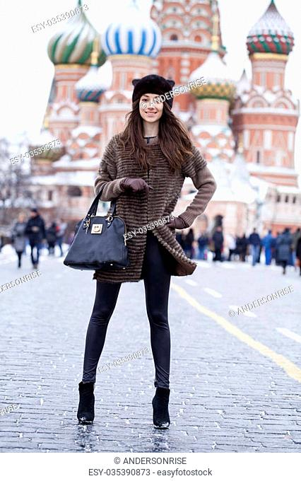 Portrait in full growth of a beautiful stylish young woman on the background of St. Basil's Cathedral, Moscow Kremlin, Russia