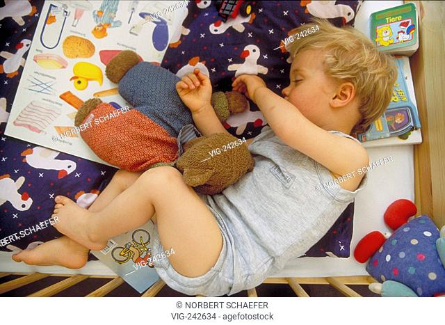 portrait, indoor, full-figure, 2-year-old blond boy wearing underwear sleeps with his toys in a bed with wooden bars  - GERMANY, 26/02/2005
