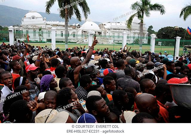 Haitians gathers for food distribution in front of the destroyed Presidential Palace in Port au Prince Haiti on Jan. 25 2010. A 7