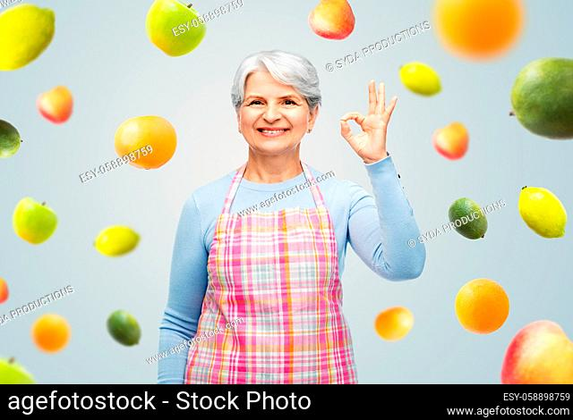 smiling senior woman in apron showing ok gesture