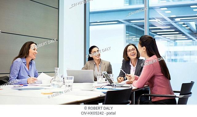 Happy businesswomen talking in conference room meeting