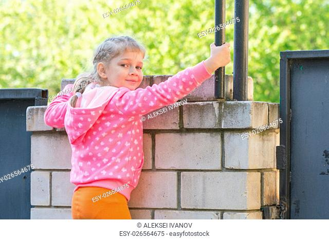 Five-year girl climbed on a brick fence and turned around looked at the frame