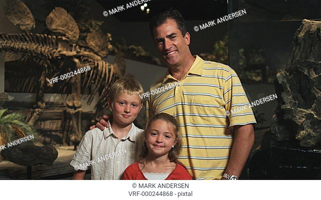MS PAN Portrait of man with daughter (8-9) and son (10-11) in natural history museum, Lehi, Utah, USA
