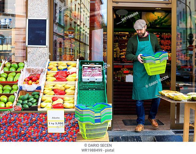 Grocer arranging shopper baskets in front of greengrocer's shop