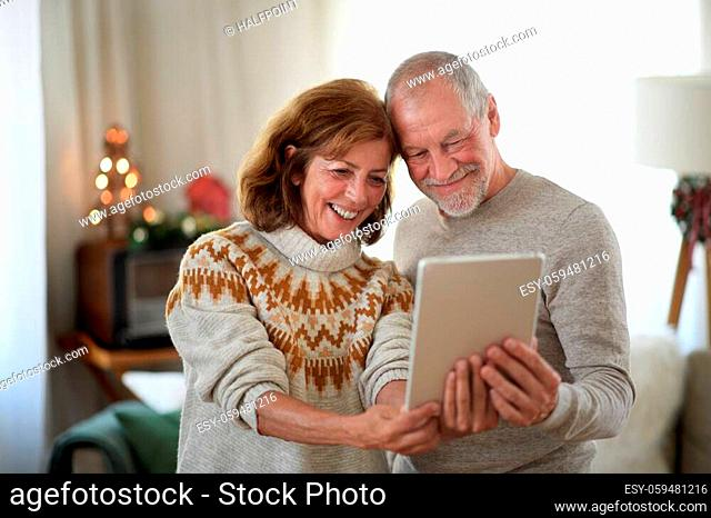 Front view of happy senior couple with tablet indoors at home at Christmas, taking selfie