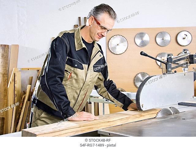 Carpenter working at circular saw