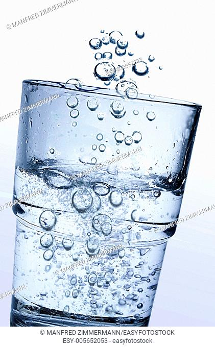 A glass of fresh clear water and lots of sparkling carbonic acid