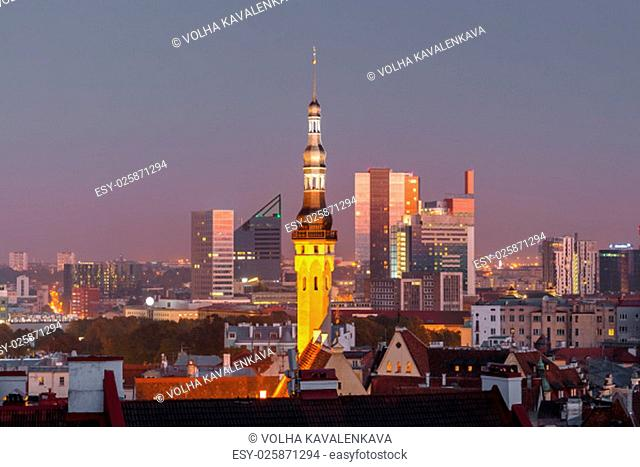 Night aerial cityscape with old town hall spire and modern office buildings skyscrapers in the background in Tallinn, Estonia