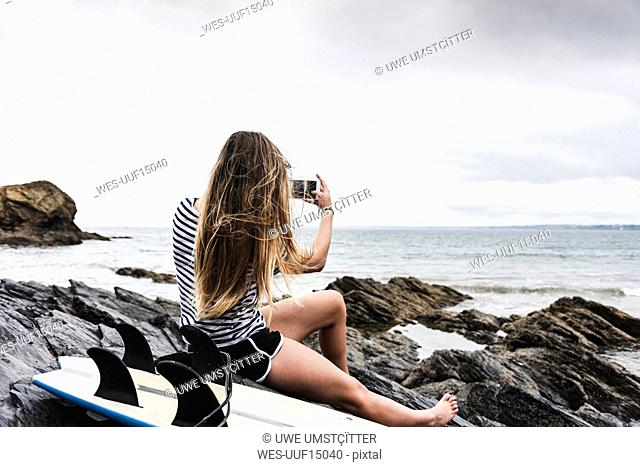Young woman with surfboard sitting on the beach, using smartphone