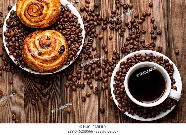 Coffee cup with coffee bean and cinnabons on wooden background. Breakfast background