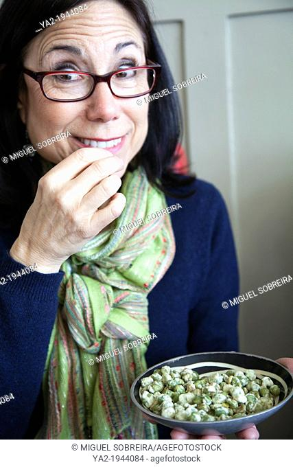 Woman eating Wasabi Pea Snack at Pub - London UK