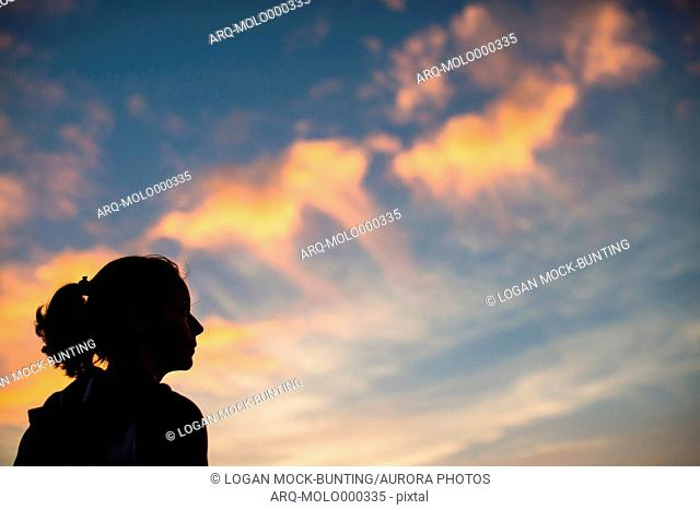 A woman's head is silhouetted against glowing clouds at sunset in Wrightsville Beach, NC