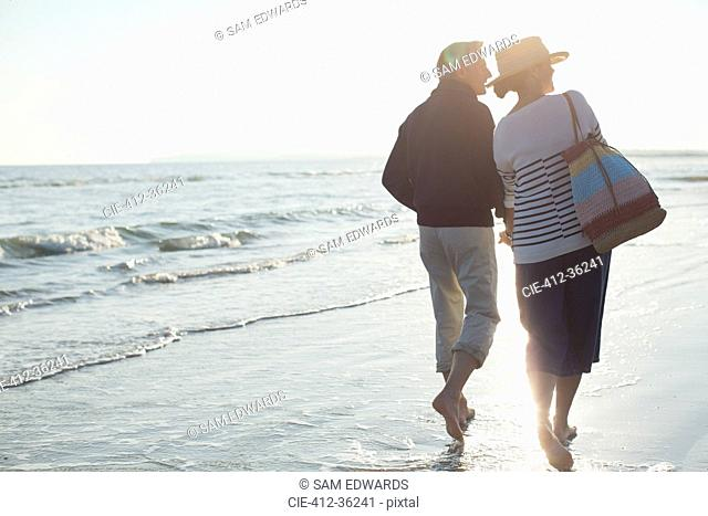 Barefoot mature couple walking on sunset beach