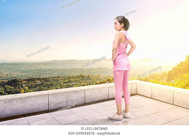 Asian athlete woman standing looking green view panorama from terrace