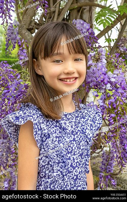 Seven year old girl standing under a wysteria tree in Honfleur, France