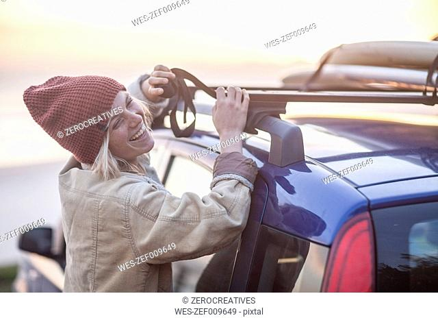 Happy young woman wearing warm clothes fastening surfboard on car roof