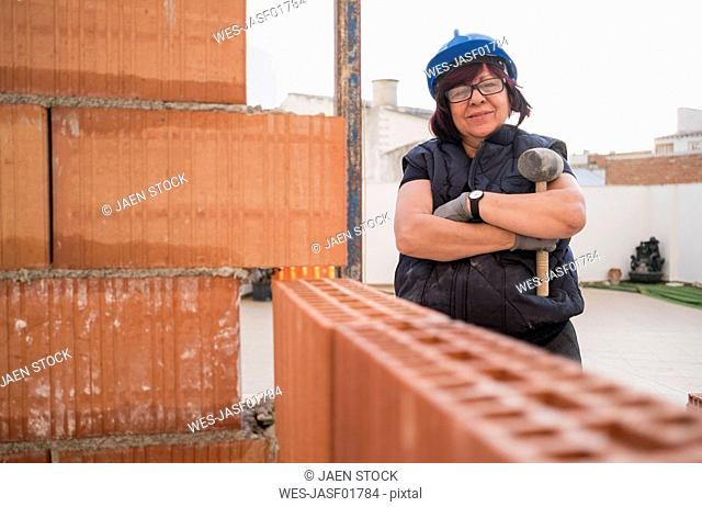 Portrait of confident senior woman building brick wall