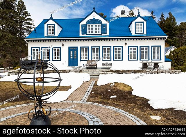 Back view of old 1920s white roughcast with blue trim cottage style house with blue steel tile roof in early spring, Quebec, Canada