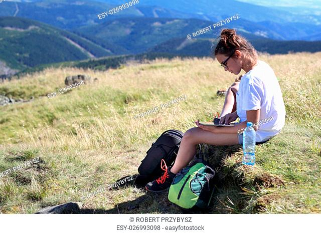 the tourist route checks trips on a mobile map. rest during a mountain hike