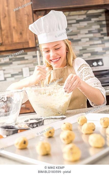 Caucasian girl baking in kitchen
