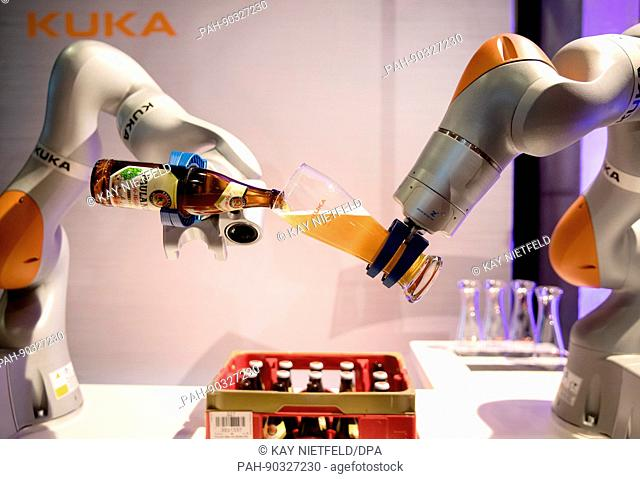 dpatop - A robot produced by the firm Kuka pours a bottle of beer into a glass during the Business20 (B20) meeting of businesses and industrial associations in...