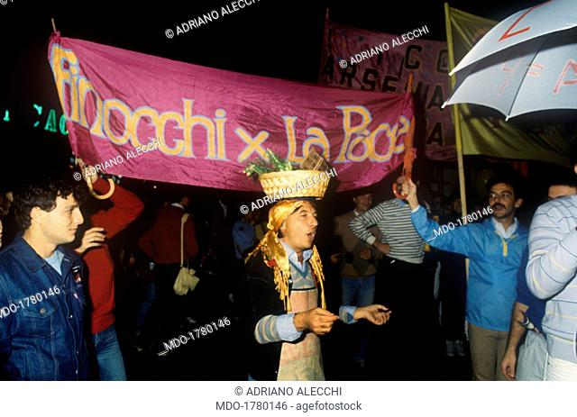 A man with a basket full of fennels on the head attending a peace demonstration. He's walking in front of a pink banner saying Fennels for peace (Finocchi per...