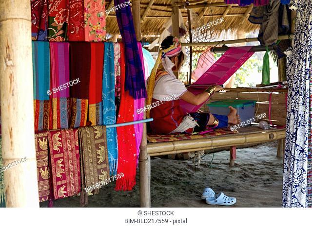 Woman weaving fabric on traditional loom in studio