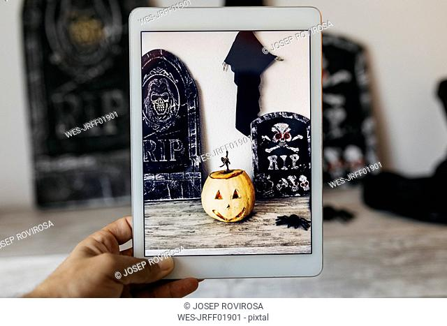 Man taking photo of Halloween decoration with digital tablet