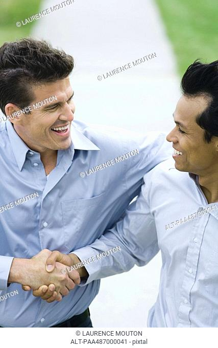 Two businessmen shaking hands, both smiling, high angle view