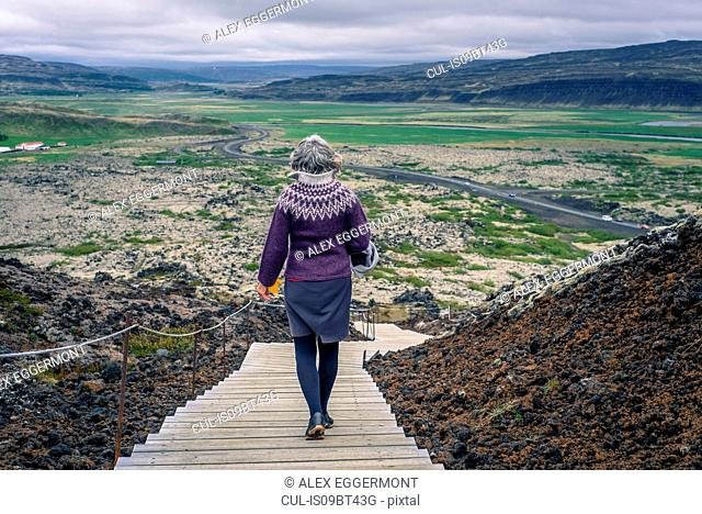 Woman walking around Grabrok volcano, Iceland