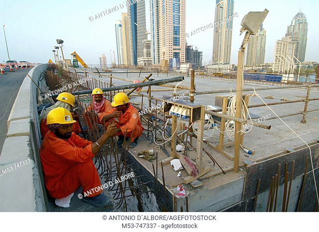 Construction workers have a rest in a building site, Marina district, Dubai, UAE
