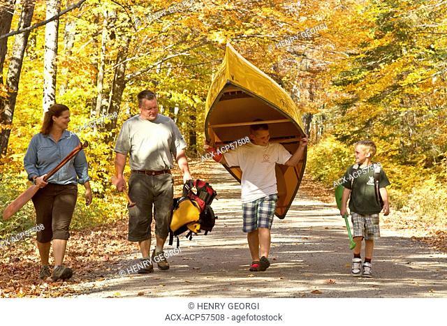Family portaging canoe, Algonquin Park, Ontario, Canada