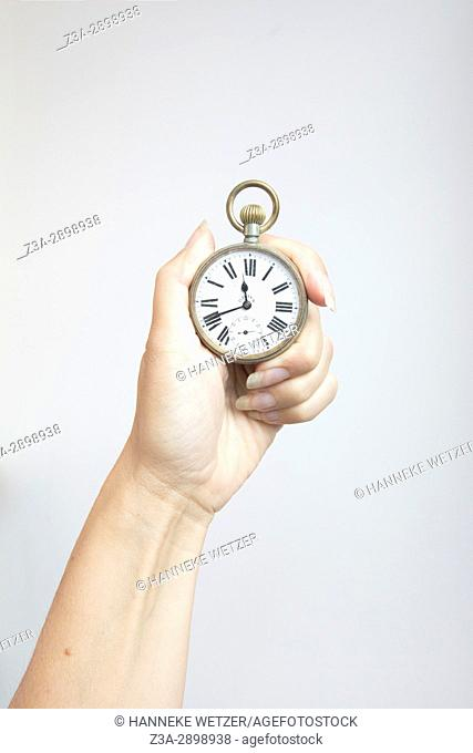 Hand holding an antique pocket watch