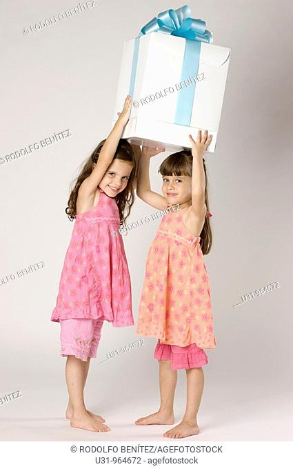 Four year old twins with a big present in a studio setting