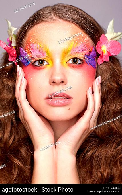 Portrait of teen girl with hands near face. Young female with unusual stylish make-up and false fashion feather eyelashes. Orchid flower in wavy hair