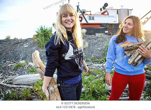 Two young women gathering firewood along coastal Homer, South-central Alaska; Homer, Alaska, United States of America