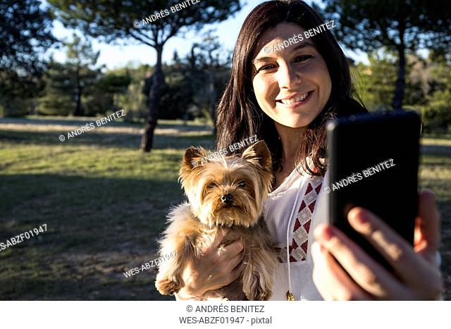 Happy young woman taking selfie with her dog