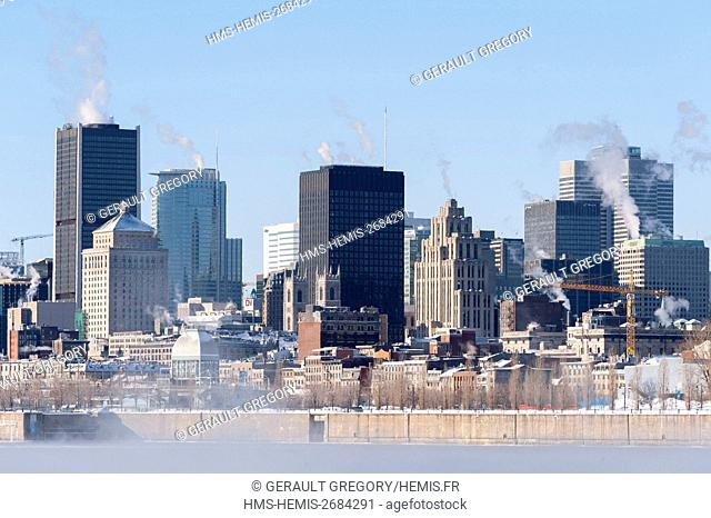 Canada, Quebec Province, Montreal, Montreal and its skyscrapers with the Saint Lawrence River icy in the foreground and misty morning smoke