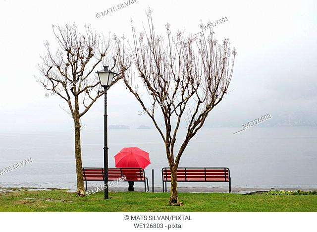 Woman sitting on a bench with a red umbrella on the lakefront in ascona ticino switzerland