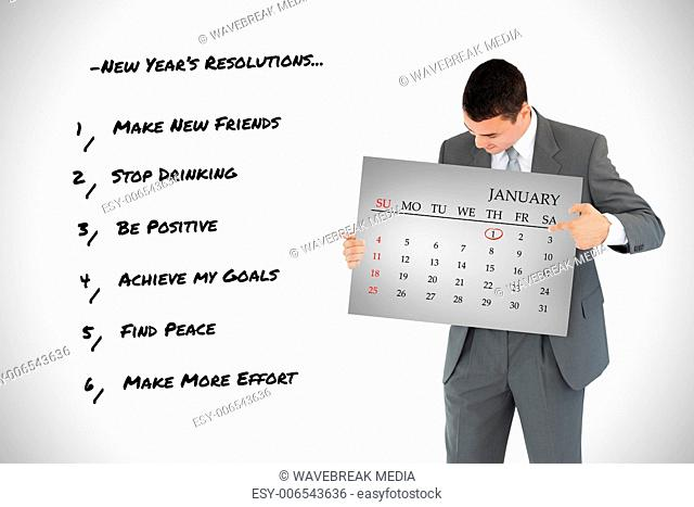 Composite image of businessman pointing at calendar in his hands