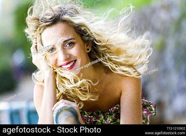 Happy young woman with strong wind blowing her curly hair away