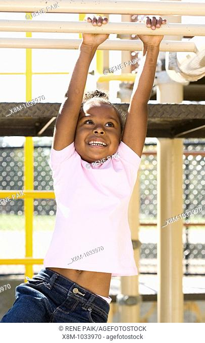 Little black girl swinging on the monkey bars in a playground