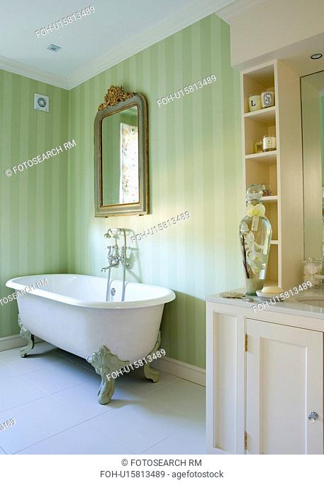 Ornate mirror above clawfoot bath in traditional bathroom with pale green striped wallpaper and white ceramic floor tiles